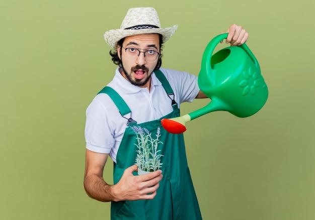 Jovem barbudo jardineiro homem vestindo macacão e chapéu segurando um regador e um vaso de planta olhando para a frente surpreso em pé sobre a parede verde claro