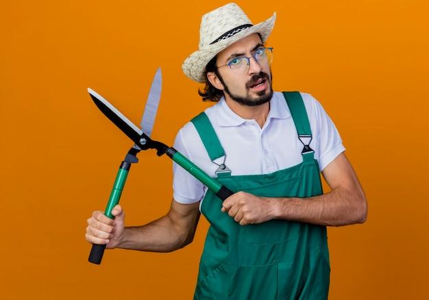 Jovem barbudo jardineiro, usando macacão e chapéu, segurando um cortador de cerca viva, olhando para a frente e ficando descontente em pé sobre a parede laranja