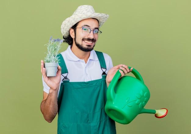 Jovem barbudo jardineiro, usando macacão e chapéu, segurando um regador e um vaso de plantas, sorrindo com uma cara feliz