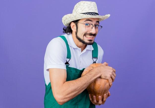 Jovem barbudo jardineiro usando macacão e chapéu segurando uma abóbora olhando para a frente sorrindo maliciosamente em pé sobre a parede azul