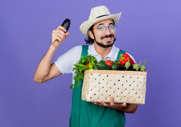 Jovem barbudo jardineiro usando macacão e chapéu segurando uma caixa cheia de vegetais mostrando berinjela sorrindo alegremente em pé sobre a parede azul