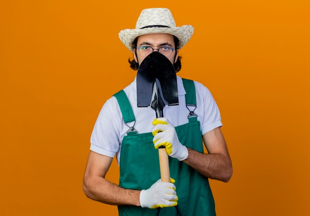 Jovem barbudo jardineiro usando macacão e chapéu segurando uma pá e escondendo o rosto em pé sobre a parede laranja