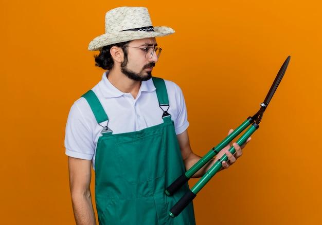 Jovem barbudo jardineiro, usando macacão e chapéu, segurando uma tesoura de cerca-viva olhando para uma tesoura com cara séria