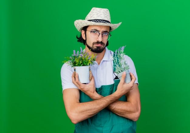 Jovem barbudo jardineiro usando macacão e chapéu segurando vasos de plantas com cara de seriou desgostoso