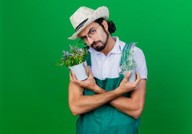 Jovem barbudo jardineiro usando macacão e chapéu segurando vasos de plantas com cara séria franzindo a testa e descontente