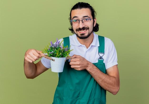 Jovem barbudo jardineiro usando macacão mostrando uma planta em um vaso sorrindo, olhando para a frente, em pé sobre a parede verde-clara