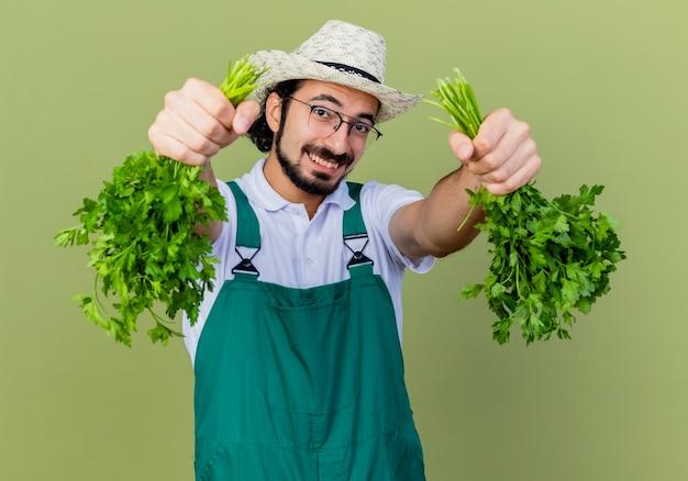 Jovem barbudo jardineiro vestindo macacão e chapéu segurando ervas frescas lookign para a câmera sorrindo com uma cara feliz