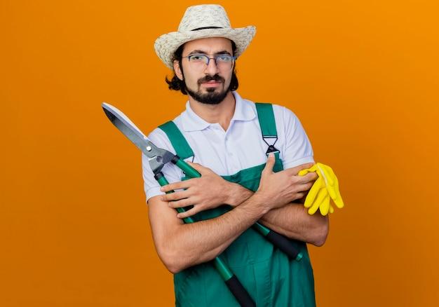 Jovem barbudo jardineiro, vestindo macacão e chapéu, segurando um cortador de cerca viva e luvas de borracha, olhando para a frente com uma cara séria em pé sobre a parede laranja