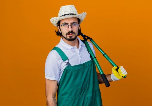 Jovem barbudo jardineiro, vestindo macacão e chapéu, segurando um cortador de cerca viva, olhando para a frente com uma cara séria em pé sobre a parede laranja