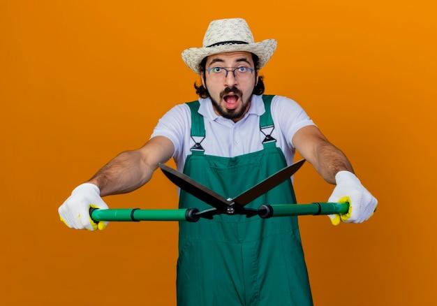 Jovem barbudo jardineiro, vestindo macacão e chapéu, segurando um cortador de cerca viva, olhando para a frente, ficando confuso e surpreso em pé sobre a parede laranja