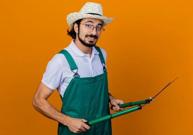 Jovem barbudo jardineiro, vestindo macacão e chapéu, segurando um cortador de cerca viva, olhando para a frente, sorrindo em pé sobre a parede laranja