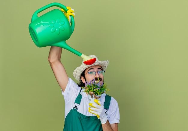 Jovem barbudo jardineiro vestindo macacão e chapéu segurando um regador e um vaso de planta molhando em pé sobre uma parede verde claro