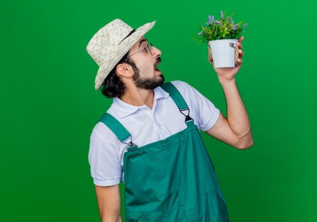 Jovem barbudo jardineiro, vestindo macacão e chapéu, segurando um vaso de planta, olhando para ele, se surpreendendo