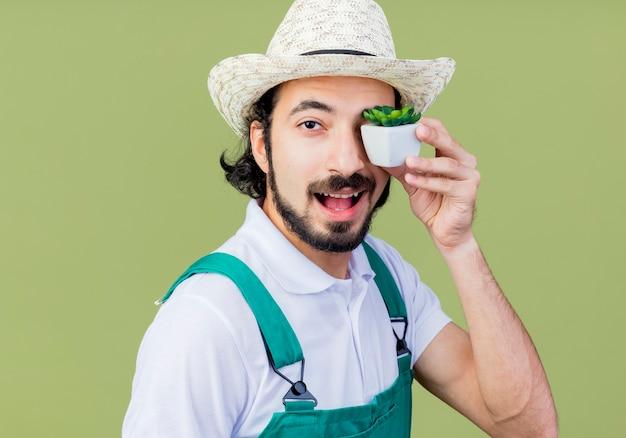 Jovem barbudo jardineiro, vestindo macacão e chapéu, segurando um vaso de plantas olhando para a frente, sorrindo em pé sobre a parede verde claro