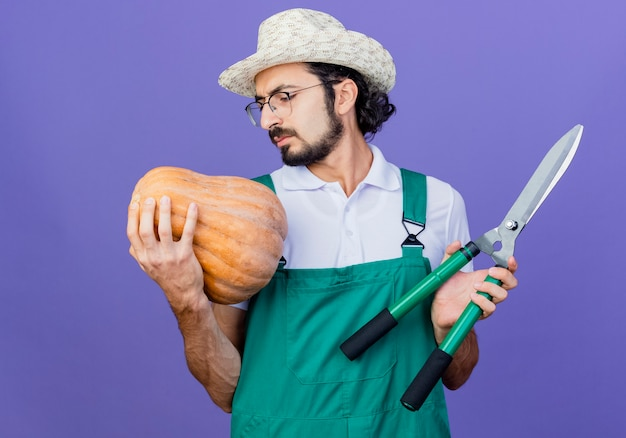 Jovem barbudo jardineiro vestindo macacão e chapéu segurando uma abóbora e um cortador de cerca viva parecendo descontente