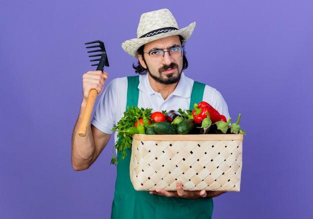 Jovem barbudo jardineiro vestindo macacão e chapéu segurando uma caixa cheia de legumes e um mini ancinho olhando para a frente com uma cara séria em pé sobre a parede azul