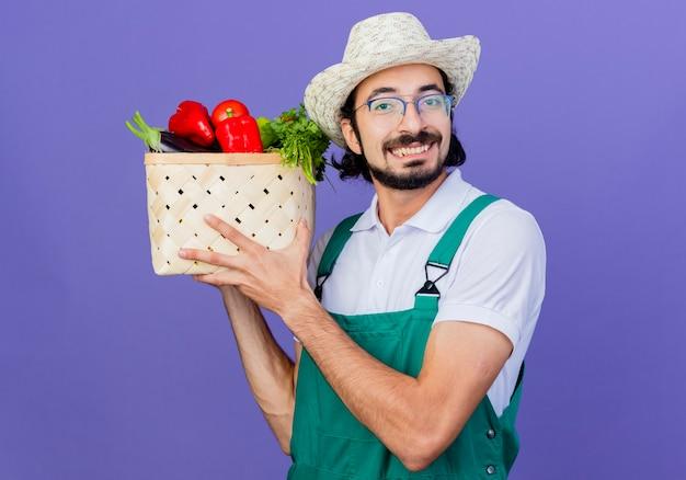 Jovem barbudo jardineiro, vestindo macacão e chapéu, segurando uma caixa cheia de legumes, olhando para a frente, sorrindo com uma carinha feliz em pé sobre a parede azul