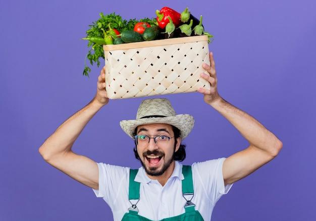 Jovem barbudo jardineiro vestindo macacão e chapéu segurando uma caixa cheia de vegetais na cabeça e sorrindo alegremente em pé sobre a parede azul