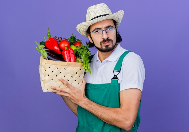 Jovem barbudo jardineiro, vestindo macacão e chapéu, segurando uma caixa cheia de vegetais, olhando para a frente com uma cara séria em pé sobre a parede azul