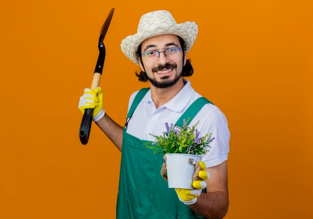 Jovem barbudo jardineiro, vestindo macacão e chapéu, segurando uma pá e um vaso de plantas olhando para a frente, sorrindo em pé sobre a parede laranja