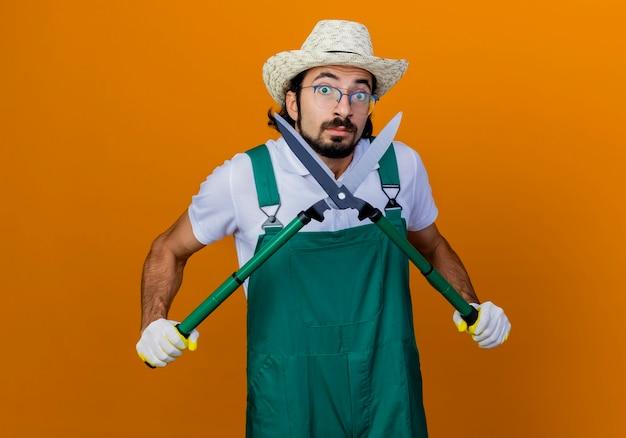Jovem barbudo jardineiro vestindo macacão e chapéu segurando uma tesoura de cerca viva lookign confuso
