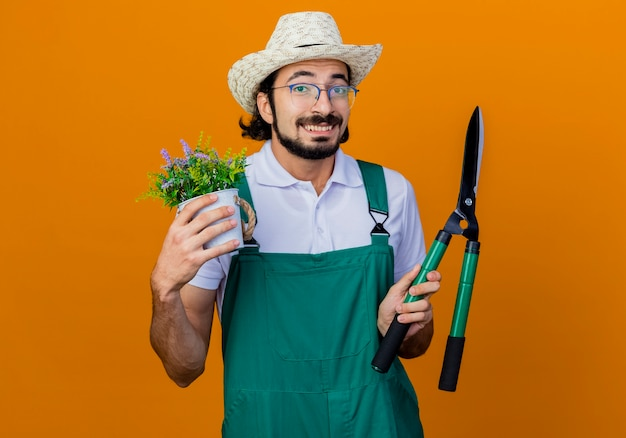 Jovem barbudo jardineiro, vestindo macacão e chapéu, segurando uma tesoura de sebes e um vaso de plantas, sorrindo alegremente