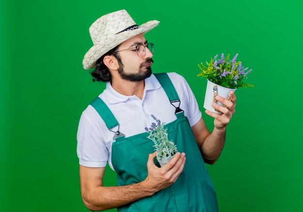 Jovem barbudo jardineiro, vestindo macacão e chapéu, segurando vasos de plantas olhando para eles com uma expressão séria