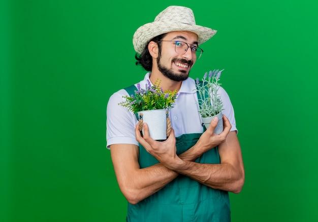 Jovem barbudo jardineiro, vestindo macacão e chapéu, segurando vasos de plantas, sorrindo com uma cara feliz