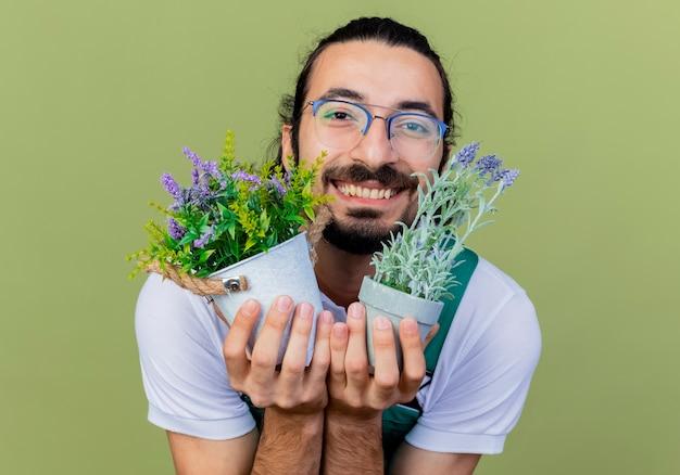 Jovem barbudo jardineiro vestindo macacão segurando vasos de plantas olhando para a frente, sorrindo alegremente em pé sobre a parede verde claro