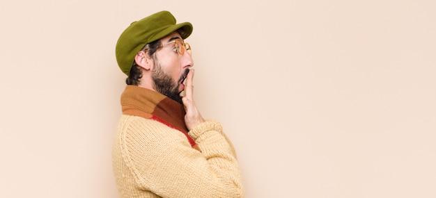 Jovem barbudo legal cobrindo a boca com as mãos com uma expressão chocada e surpresa, mantendo um segredo ou dizendo oops