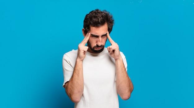 Jovem barbudo louco com dor de cabeça