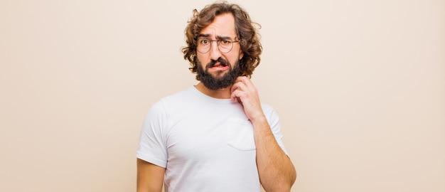 Jovem barbudo louco se sentindo estressado, frustrado e cansado, esfregando o pescoço doloroso, com um olhar preocupado e preocupado