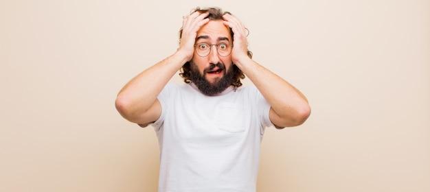 Jovem barbudo louco se sentindo horrorizado e chocado, levantando as mãos na cabeça e entrando em pânico por um erro contra a cor lisa
