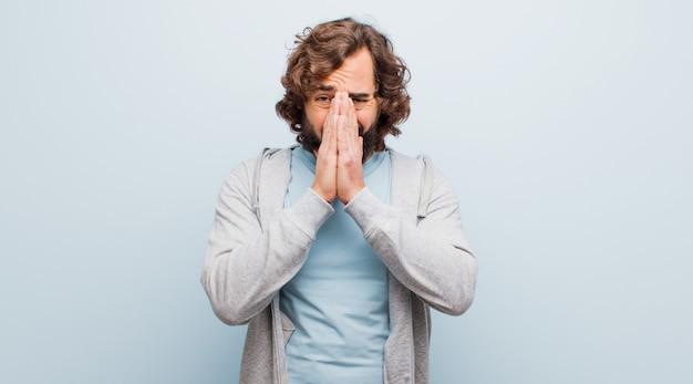 Jovem barbudo louco se sentindo preocupado, esperançoso e religioso, orando fielmente com as palmas das mãos pressionadas, pedindo perdão contra a cor lisa
