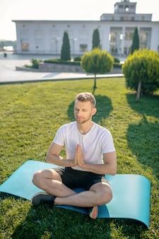 Jovem barbudo meditando do lado de fora, com as mãos no namaste