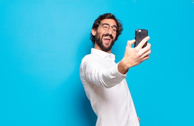 Jovem barbudo mostrando a tela do celular