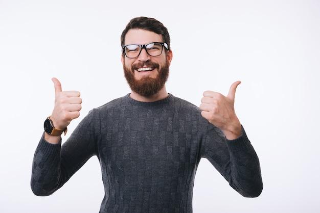 Jovem barbudo na camisola com óculos está aparecendo os polegares sobre um fundo branco.