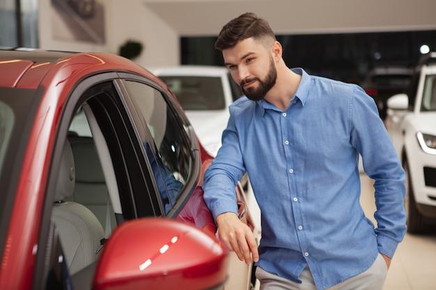 Jovem barbudo olhando para um carro novo no salão da concessionária, copie o espaço
