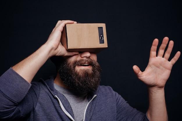 Jovem barbudo olhando por um fone de ouvido de papelão para realidade virtual
