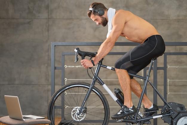 Jovem barbudo ouvindo música e andando de bicicleta papelaria
