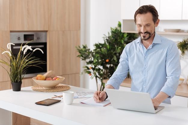 Jovem barbudo parado atrás do balcão da cozinha, trabalhando no laptop e escrevendo algo no caderno enquanto sorri