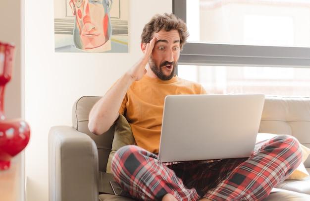 Jovem barbudo parecendo feliz espantado e surpreso sorrindo e percebendo uma boa notícia incrível e sentado com um laptop