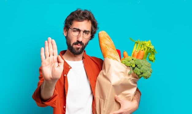 Jovem barbudo parecendo sério, severo, descontente e irritado, mostrando a palma da mão aberta fazendo gesto de pare e segurando uma sacola de legumes