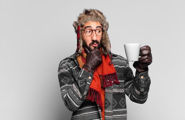Jovem barbudo pensando e vestindo roupas de inverno