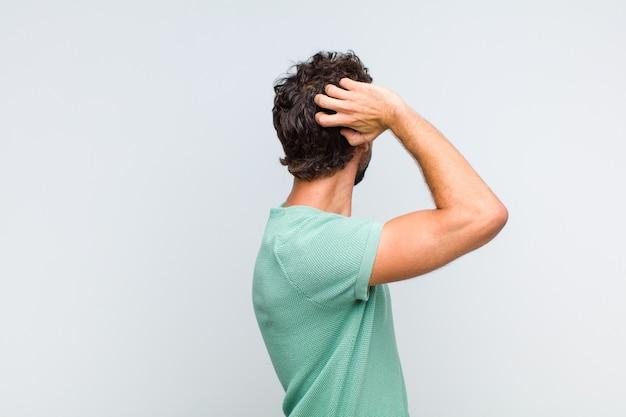 Jovem barbudo pensando ou duvidando, coçando a cabeça, sentindo-se perplexo e confuso, visão traseira ou traseira