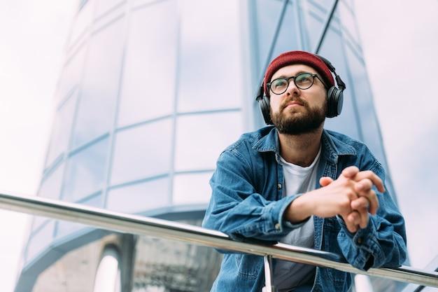 Jovem barbudo pensativo vestido com camisa jeans gosta de mísseis em fones de ouvido na cidade. olhando para longe.
