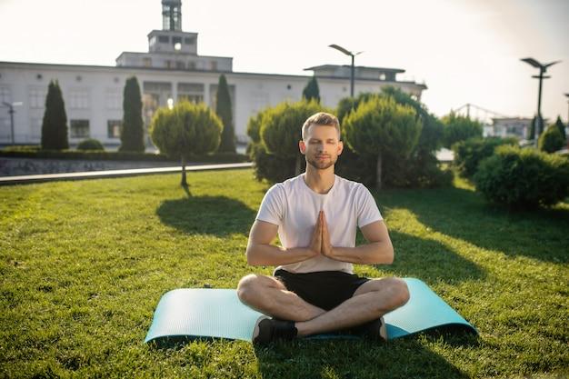 Jovem barbudo praticando ioga ao ar livre, com as mãos namastê