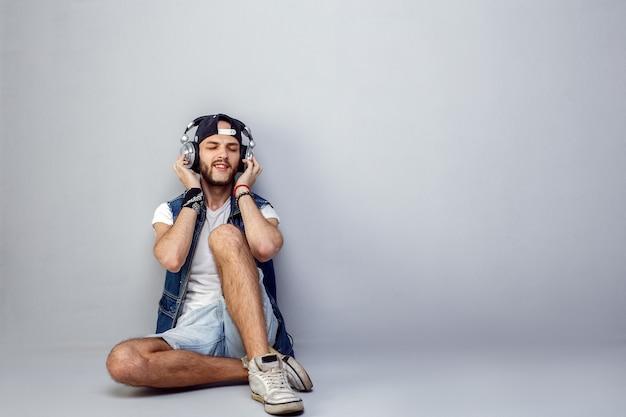 Jovem barbudo relaxado em fones de ouvido