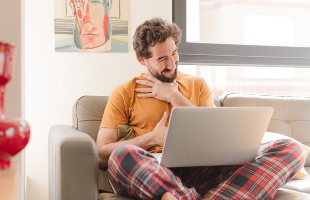 Jovem barbudo rindo alto de uma piada hilária, sentindo-se feliz e alegre, se divertindo e sentado com um laptop