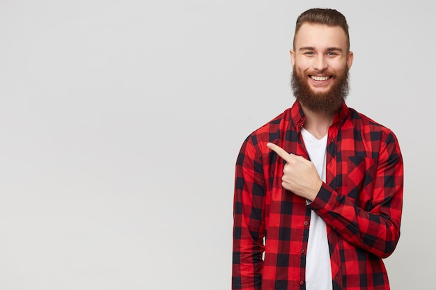 Jovem barbudo satisfeito feliz com camisa quadriculada sorrindo alegremente apontando com o dedo indicador para a esquerda, sobre fundo branco